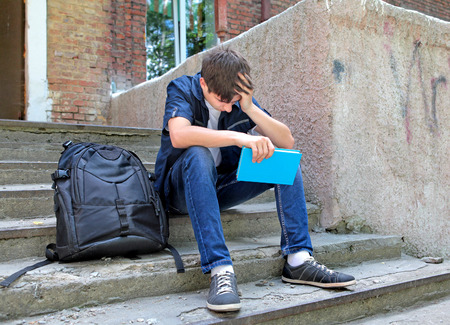 school exam: Sad Student with the Book on the landing steps