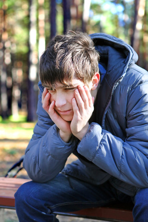 Sad Teenager sitting in the Autumn park photo