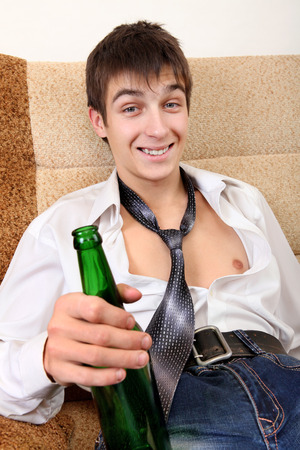 beer necktie: Drunken Teenager with Bottle of the Beer on the Sofa at the Home Stock Photo