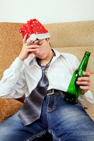 beer and necktie: Drunken Teenager in Santa Hat sleeping on the Sofa at the Home with the Beer Stock Photo