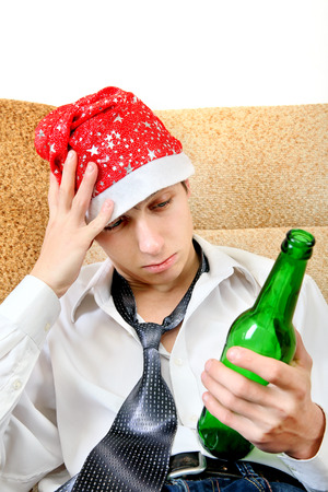 beer necktie: Sad and Tired Teenager with Bottle of the Beer and Santa Hat on the Sofa at the Home
