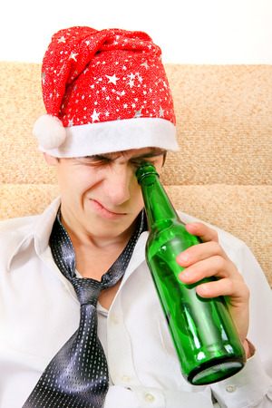 necktie beer: Teenager in Santa Hat looking into the Empty Bottle of the Beer on the Sofa Stock Photo