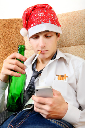 beer necktie: Teenager in Santa Hat with Bottle of the Beer and Cellphone on the Sofa at the Home