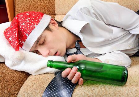 Drunken Teenager sleeping in Santa Hat and Bottle of the Beer on the Sofa