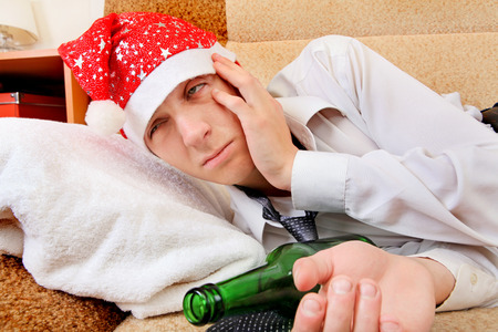 necktie beer: Sad and Tired Teenager with Bottle of the Beer and Santa Hat on the Sofa at the Home