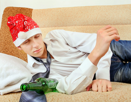 drowse: Sad and Tired Teenager with Bottle of the Beer and Santa Hat on the Sofa at the Home