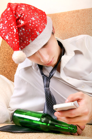 beer and necktie: Sad and Tired Teenager in Santa Hat with Bottle of the Beer and Cellphone on the Sofa Stock Photo