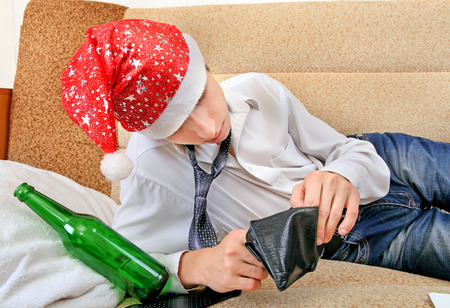 beer and necktie: Teenager in Santa Hat Checking Empty Wallet after Party on the Sofa