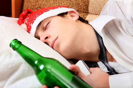 necktie beer: Teenager sleeping in Santa Hat and Bottle of the Beer on the Sofa Stock Photo