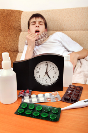 Focus on the Clock. Sick Teenager taking a Pill on the Bed at the Home photo