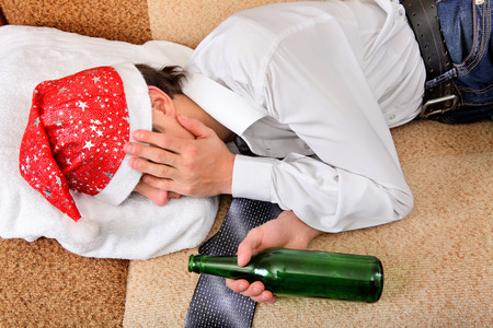 beer and necktie: Drunken Teenager sleeping in Santa Hat and Bottle of the Beer on the Sofa