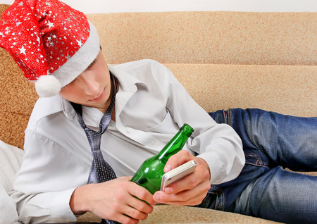 beer necktie: Sad and Tired Teenager in Santa Hat with Bottle of the Beer and Cellphone on the Sofa Stock Photo