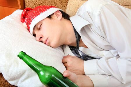 beer necktie: Drunken Teenager sleeping in Santa Hat and Bottle of the Beer on the Sofa