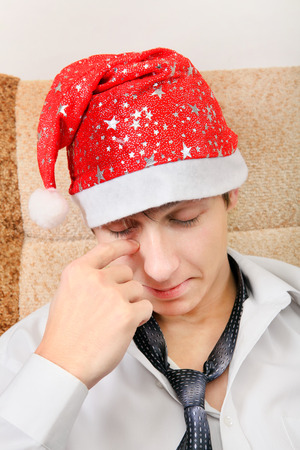 Sad and Tired Teenager in Santa Hat on the Sofa at the Home photo