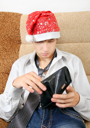 necktie beer: Teenager in Santa Hat Checking Empty Wallet on the Sofa at the Home Stock Photo
