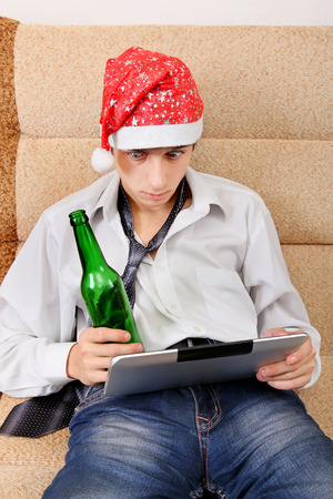 beer necktie: Surprised Teenager in Santa Hat with Tablet Computer and Bottle of the Beer
