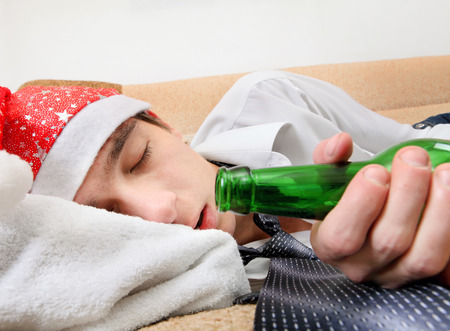 necktie beer: Drunken Teenager sleeping in Santa Hat and Bottle of the Beer on the Sofa
