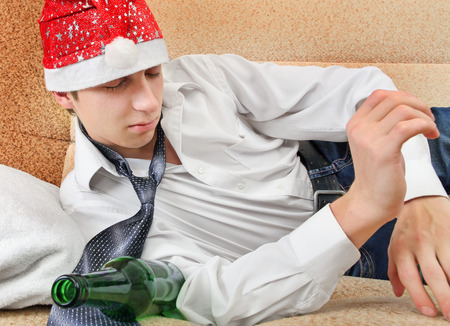 necktie beer: Drunken Teenager with Bottle of the Beer and Santa Hat on the Sofa at the Home