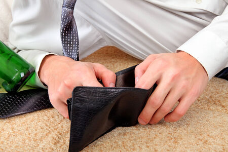 beer and necktie: Person Checking Empty Wallet after Party on the Sofa closeup Stock Photo