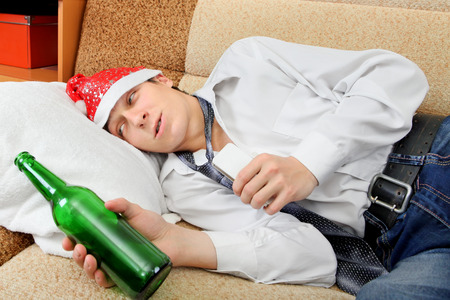 beer and necktie: Drunken Teenager with Bottle of the Beer and Santa Hat on the Sofa at the Home