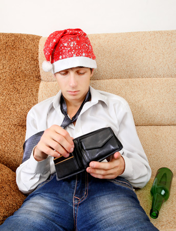 beer and necktie: Teenager in Santa Hat Checking Empty Wallet on the Sofa at the Home Stock Photo