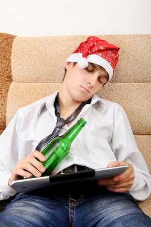 necktie beer: Tired Teenager sleeping in Santa Hat with Tablet Computer and Bottle of the Beer