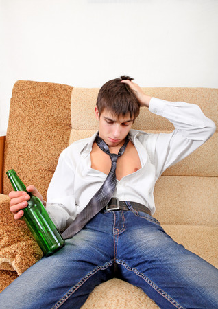 beer necktie: Teenager with Bottle of the Beer on the Sofa at the Home Stock Photo
