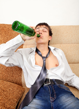 beer necktie: Teenager drinks a Beer on the Sofa at the Home
