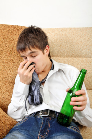 necktie beer: Drunken Teenager with Bottle of the Beer on the Sofa at the Home Stock Photo