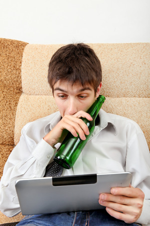 necktie beer: Stressed and Tired Teenager with a Beer and Tablet Computer on the Sofa at the Home
