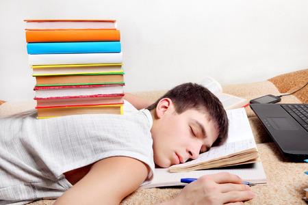 Tired Teenager sleep on the Sofa with the Books photo