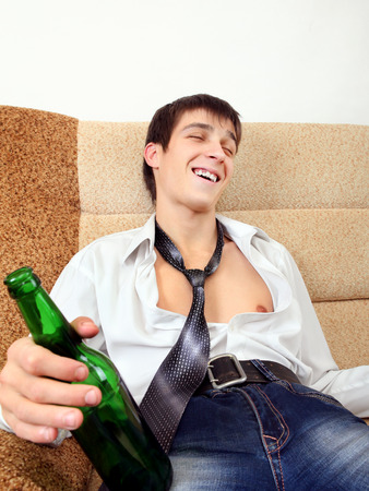 beer necktie: Drunken Young Man with Bottle of the Beer on the Sofa at the Home