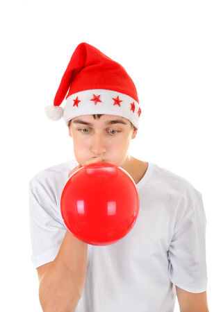 inflate: Teenager in Santas Hat inflate Red Balloon Isolated On The White Background