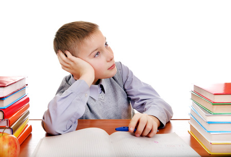 Bored Kid on the School Desk Isolated on the white background photo