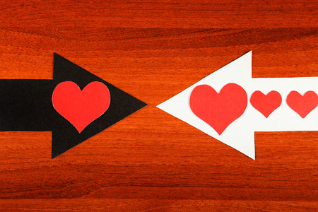 romance strategies: Heart Shapes on the Black and White Arrows on the Wooden Background