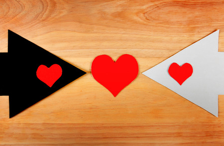 Heart Shapes on the Black and White Arrows on the Wooden Background photo