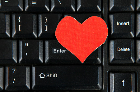 Red Heart Shape on the Computer Keyboard closeup photo