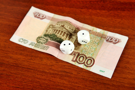roubles: Hundred Russian Roubles and Dices on the Wooden Background