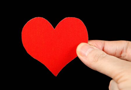 Red Heart Shape in the Hand on the Black Background photo