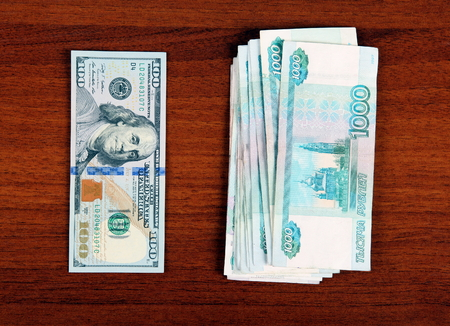 roubles: Russian Roubles and American Dollars on the Wooden Background