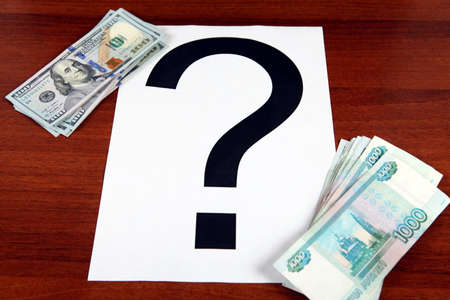 roubles: Russian Roubles and American Dollars with Question Mark on the Wooden Background