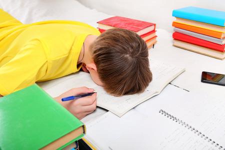 tearful: Sad and Tired Teenager doing Homework at the Home