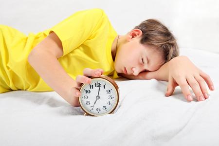 reveille: Kid sleep with Alarm Clock on the Bed