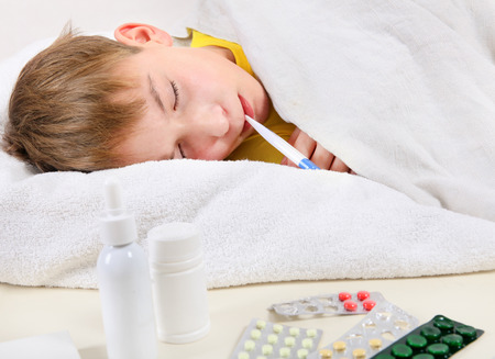 diseased: Sick Kid with Thermometer in the Bed Stock Photo