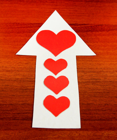romance strategies: Red Heart Shapes on the Arrow and on the Wooden Background