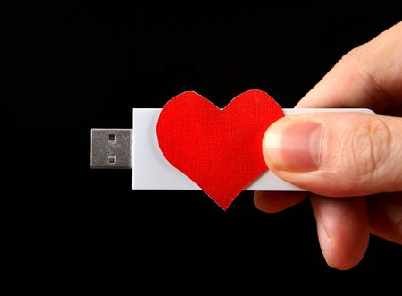 usb drive: Heart Shape and USB Drive in the Hand on the Black Background Stock Photo