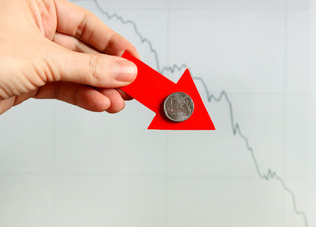 slump: Red Arrow in a Hand with Russian Ruble Down on the Diagram Background Stock Photo