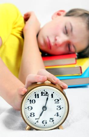reveille: Kid sleep with Alarm Clock on the Bed. Focus on the Clock