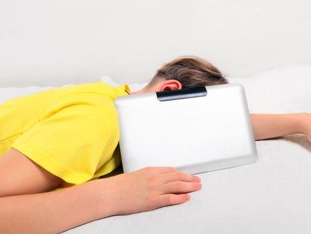 boyhood: Tired Kid sleep with Tablet Computer on the Bed