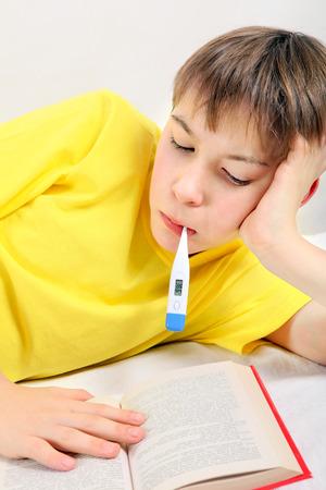 sick kid: Ni�o enfermo con un libro y term�metro en la cama